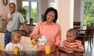black family influencers in kitchen drinking orange juice