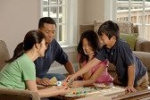 happy-asian-pacific-family-playing-monopoly-at-home