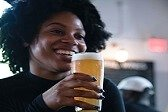 black female social media influencer drinking glass of beer