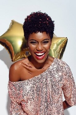 smiling-black-female-influencer-wearing-silvery-sequins-off-the-shoulder-shirt-holding-gold-mylar-balloons