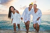 three-women-of-color-walking-on-the-sand-in-front-of-the-ocean-laughing