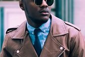 black male social media influencer wearing brown leather jacket and sunglasses