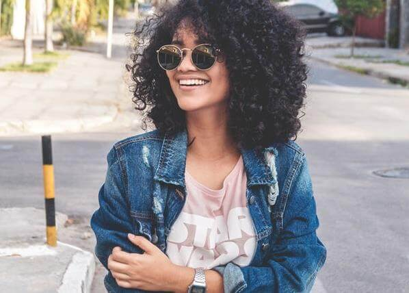 female-social-media-influencer-wearing-jean-jacket-and-star-wars-tee-shirt-smiling-standing-on-street