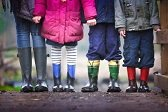 children standing next to each other wearing rain jackets and boots