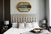 tastefully decorated bedroom with a beige tufted panel bedroom set and throw pilliows