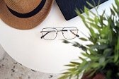 influencer product review of straw hat, black wallet and glasses sitting on white table