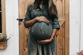 mother-to-be-influencer-wearing-green-dress-holding-her-pregnant-belly