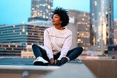 black-female-travel-influencer sits outside on rooftop of hotel she is reveiwing
