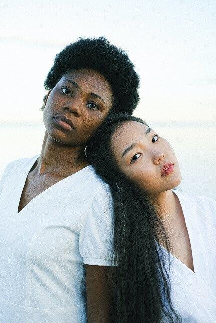 black-woman-wearing-white-shirt-leaning-against-asian-pacific-woman-wearing-white-shirt