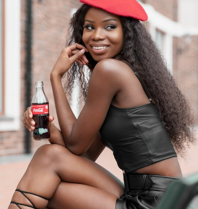 black female influencer sits wearing red beret hat and a crop leather top and skirt holding a coca cola bottle smiling
