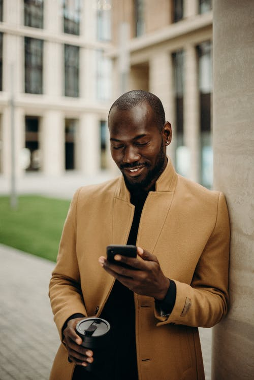 black influencer looks at phone smiling