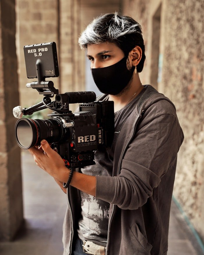 BME-video-content-creator-holding-red-pro-5-video-camera-wearing-black-facial-ppe-mask