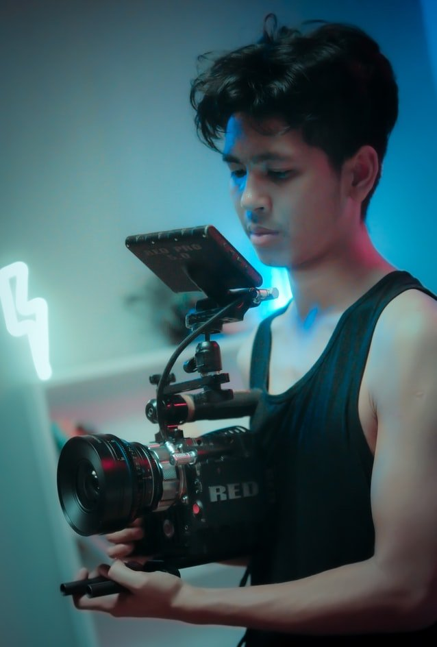 asian-american-video-content-creator holding camera while filming