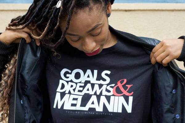 black-women-wearing-leather-jacket-black-tee-shirt-with-goals-dreams-melanin-white-font