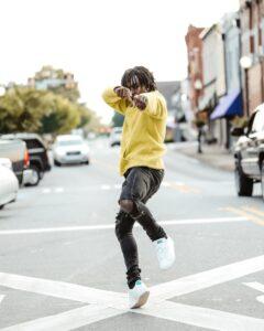 black-male-influencer-dancing-in-street-wearing-yellow-sweatshirt-white-sneakers