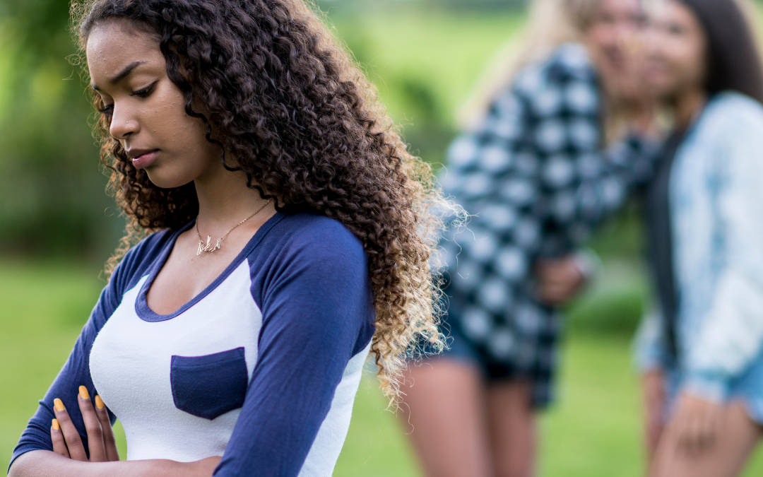 BIPOC-young-woman-stands-arms-crossed-looking-depressed-while-two-white-young-women-whisper-behind-her-outside-at-a-park